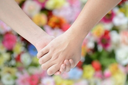 手をつなぎ合うカップル